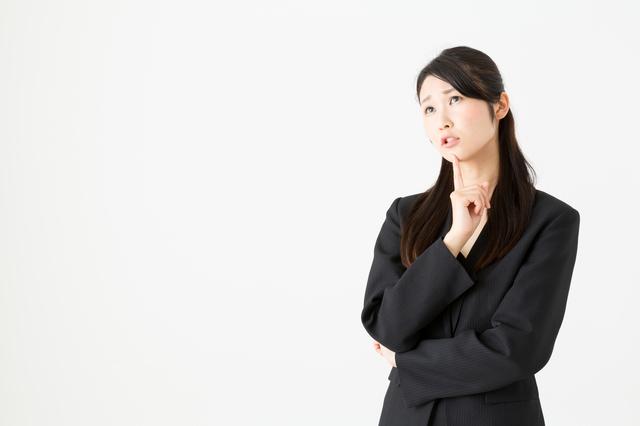 顎に手を当てて悩むスーツ姿の女性