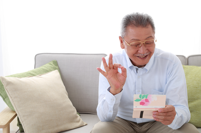 通帳を見て微笑む男性
