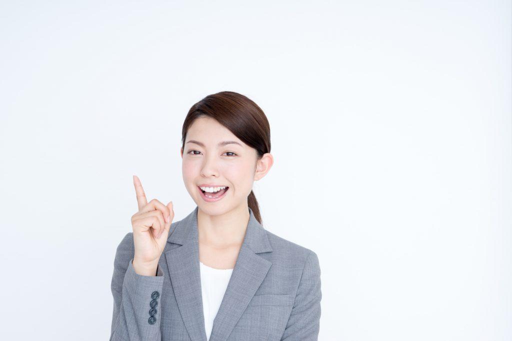 人差し指をたてるスーツ姿の女性