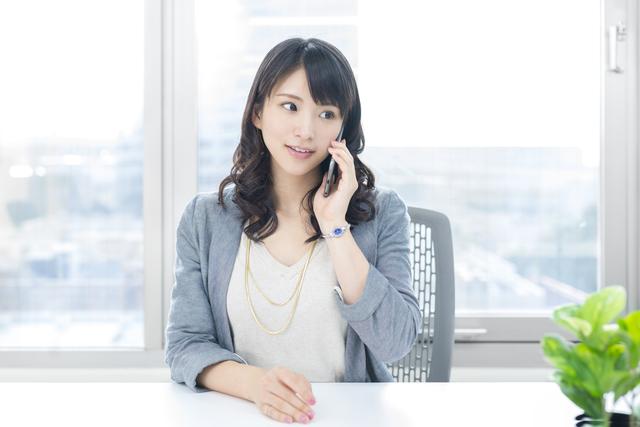 職場で電話をかける女性